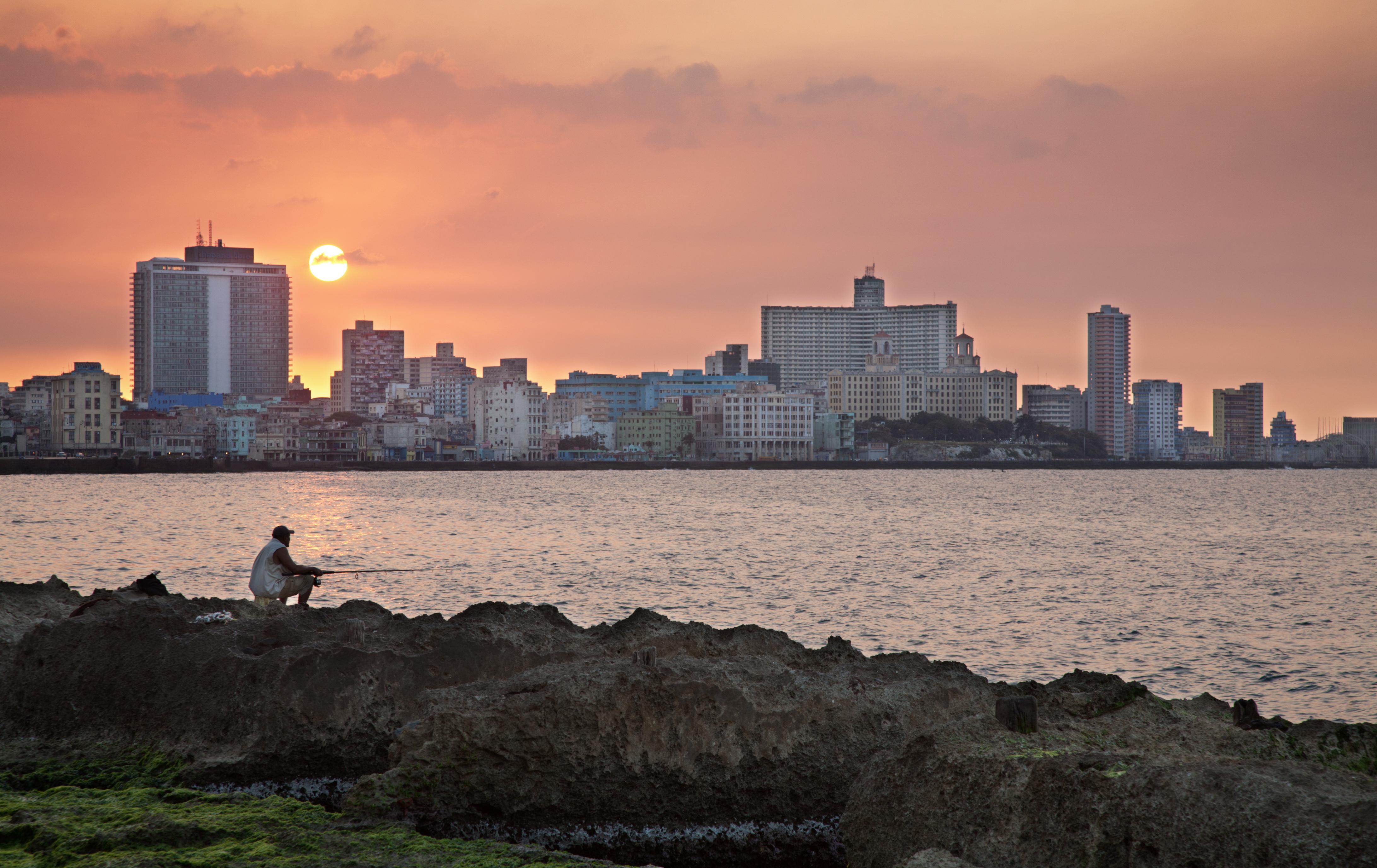 Fishing at the Malecon at sunset. At the back, the Hotel Nacional in Vedado. Havana (La Habana), Cuba