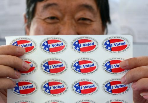 """Election official Henry Tung displays a sheet of """"I Voted"""" stickers in various  languages at a polling station at St. Paul's Lutheran Church in Monterey Park, Los Angeles County, on November 6, 2012 in California, as Americans flock to the polls nationwide to decide between President Barack Obama, his Rebuplican challenger Mitt Romney, and a wide range of other issues. Monterey Park is one of six cities in California's 49th Assembly District, the state's first legislative district where Asian-Americans make up the majority of the population.     AFP PHOTO/Frederic J. BROWN        (Photo credit should read FREDERIC J. BROWN/AFP/Getty Images)"""