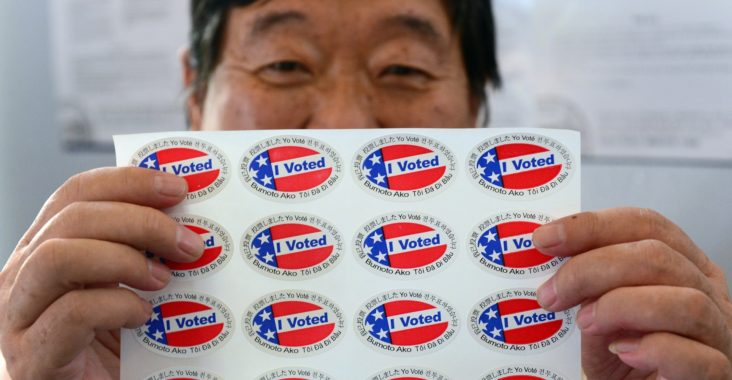 "Election official Henry Tung displays a sheet of ""I Voted"" stickers in various  languages at a polling station at St. Paul's Lutheran Church in Monterey Park, Los Angeles County, on November 6, 2012 in California, as Americans flock to the polls nationwide to decide between President Barack Obama, his Rebuplican challenger Mitt Romney, and a wide range of other issues. Monterey Park is one of six cities in California's 49th Assembly District, the state's first legislative district where Asian-Americans make up the majority of the population.     AFP PHOTO/Frederic J. BROWN        (Photo credit should read FREDERIC J. BROWN/AFP/Getty Images)"